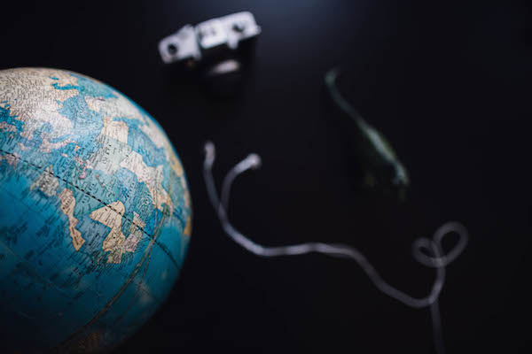 Image of a globe, earbuds and camera