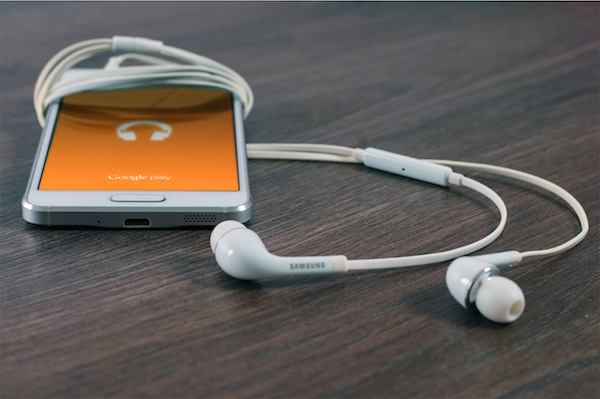 image of earbuds and a smartphone to listen to podcasts