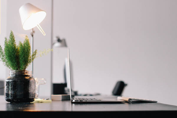 Copywriter's desk with laptop, desk lamp and plant