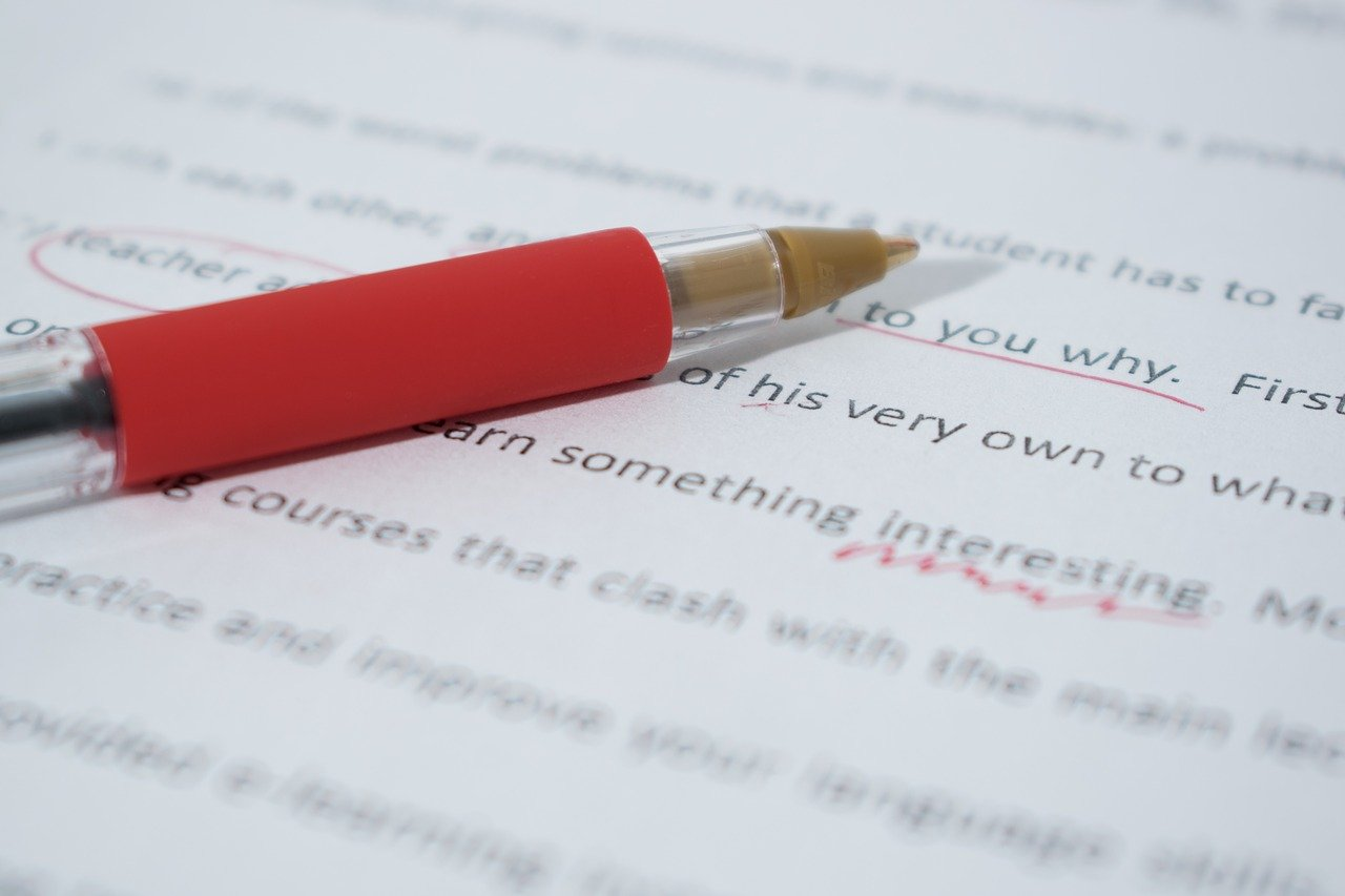 proofreading pen on paper with markups