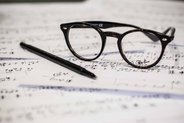 Sheets of music with eyeglasses and a pen on top.